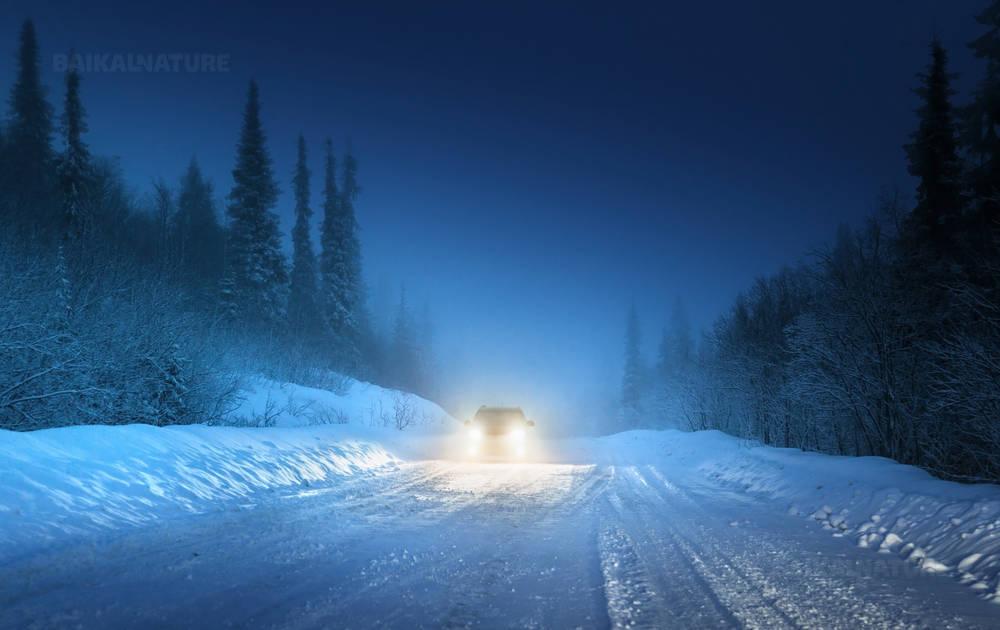 Автомобильные фары на машине двигающийся по дороге через зимний лес в России.