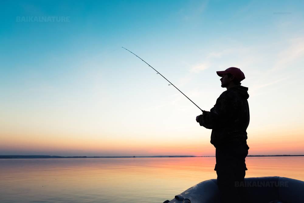 Человек рыбачующий с лодки на закате солнца.