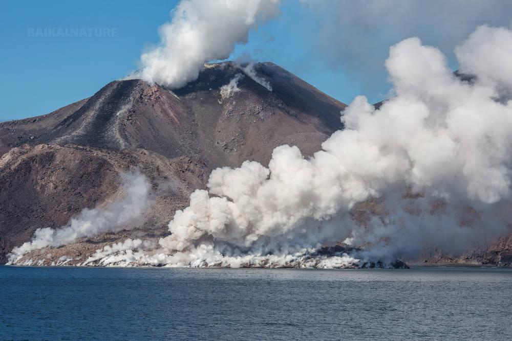 Остров Чирпой, белый дым вулканической активности.