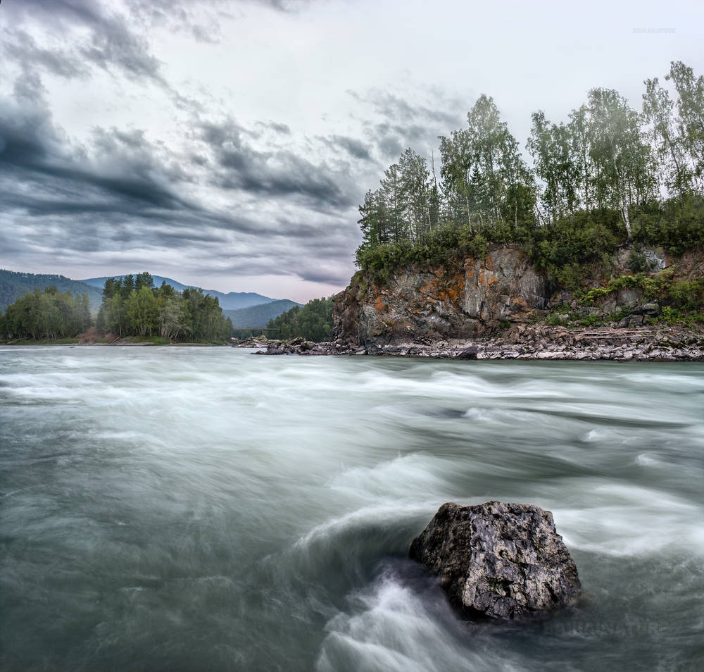 Пейзаж горной реки с камнем.
